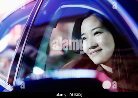 Smiling woman looking through car window at the city nightlife, reflected lights - Stock Photo