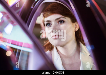 Serene businesswoman opening car door at night, close-up, reflected lights - Stock Photo