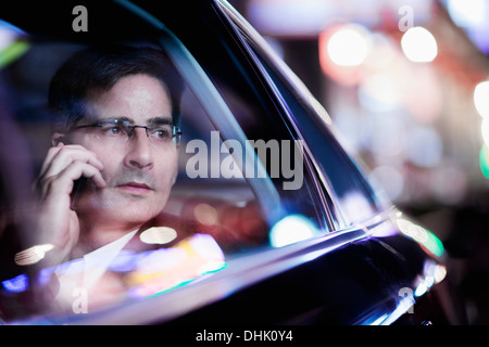 Businessman on the phone and looking out the car window at night, reflected lights - Stock Photo