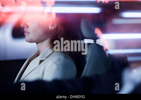 Serene businesswoman sitting in the car at night, illuminated and reflected lights on the car window - Stock Photo