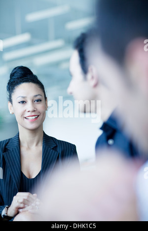 Young businesswoman sitting in a business meeting with colleagues - Stock Photo