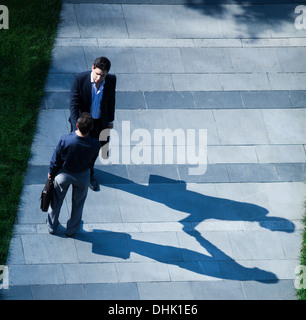 Aerial view of two businessmen shaking hands on the sidewalk - Stock Photo