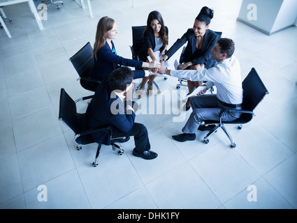 Business people sitting in a circle with hands together cheering - Stock Photo