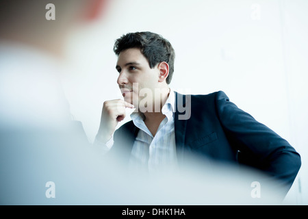 Young businessman listening in a business meeting - Stock Photo