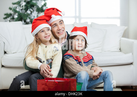 Father And Siblings Wearing Santa Hats During Christmas - Stock Photo