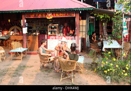 People sitting  outside a coffee shop in Varkala,India. - Stock Photo