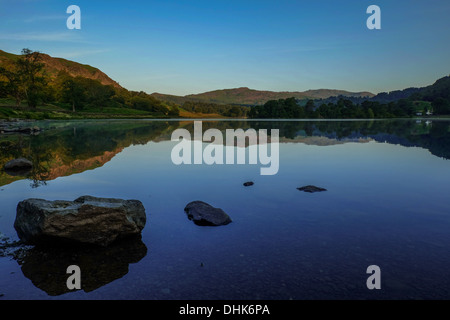 Rydal Water at sunrise, shot low across the water towards the fells in the background with stones in the foreground - Stock Photo