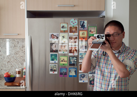 Instant photography, revived by the Impossible Project. An Asian man takes a Polaroid in front of a fridge full - Stock Photo
