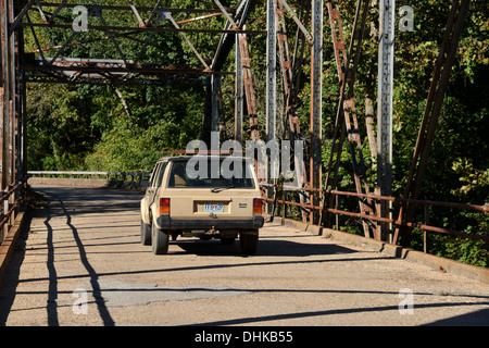 Old Jeep Cherokee SUV drives over an truss girder box bridge crosses a river on old Route 66 in rural Missouri, - Stock Photo