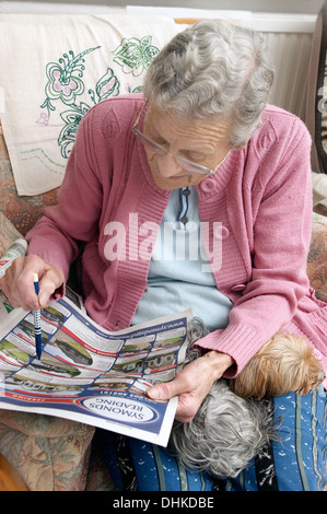 Elderly woman looking at properties on the property pages in a local paper & marking off anything interesting - Stock Photo