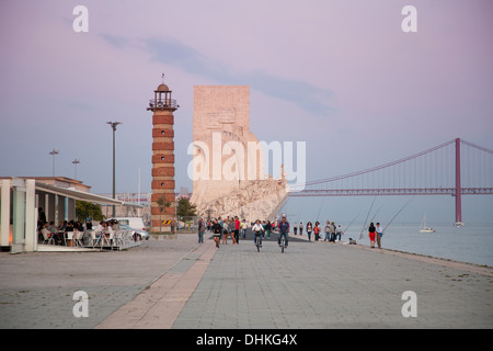 Padrao dos Descobrimentos, Discoveries Monument in Belem and Ponte 25 de Abril bridge over the Tagus river at sunset, - Stock Photo