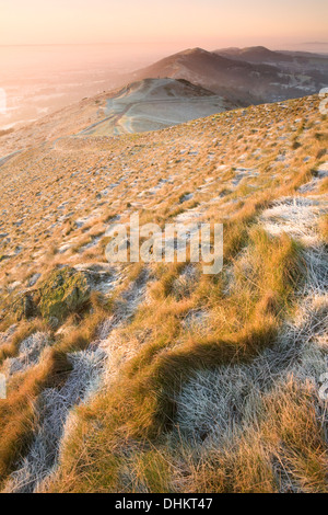 Sun rises over the Malvern hills casting shadows and highlights on the frosted tufts of grass on the Worcestershire - Stock Photo