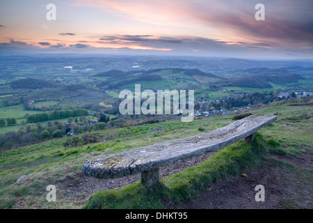 An old weathered wooden bench on the West side of the Worcesteshire Beacon, Malvern, at sunset. - Stock Photo