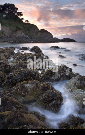 Swirling water around the jagged jocks as the tide comes in at Lee Bay, Devon, England as the sun sets in the background - Stock Photo