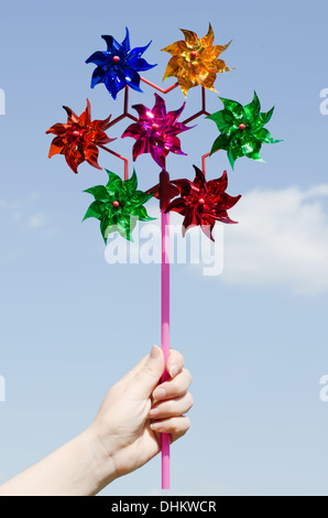 Children's hand holding a toy windmill - Stock Photo