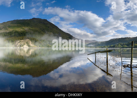 A wire fence and reflection going into Llyn Gwynant. The mist rising over the lake partially obscures Gallt y Wenallt - Stock Photo