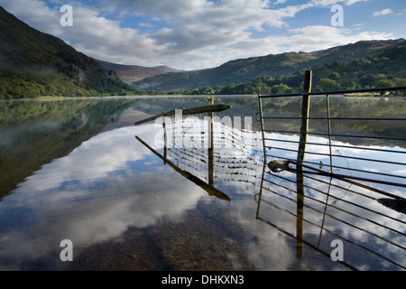 A fence and reflection going into Llyn Gwynant. The mist rising over the lake partially obscures Gallt y Wenallt, - Stock Photo