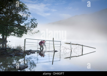 Photographer in a red coat taking a photograph of a fence and reflection going into Llyn Gwynant, Snowdonia, Wales. - Stock Photo