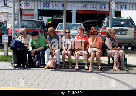 Group of adults sitting on bench waiting for the bus or tram. Warsaw Poland - Stock Photo