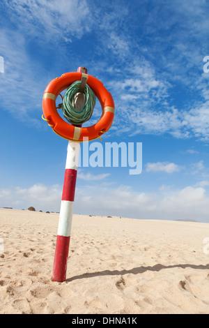 lifebuoy on a column in the desert - Stock Photo
