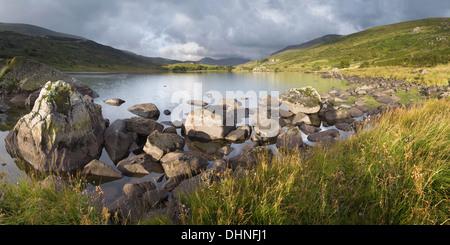 Sunrise over Llynnau Mymbyr. It was raining on the far side of the lake towards Snowdon, creating a rainbow. - Stock Photo