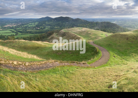 A path winds through the levels in British Camp towards the Malvern Hills at sunrise. - Stock Photo