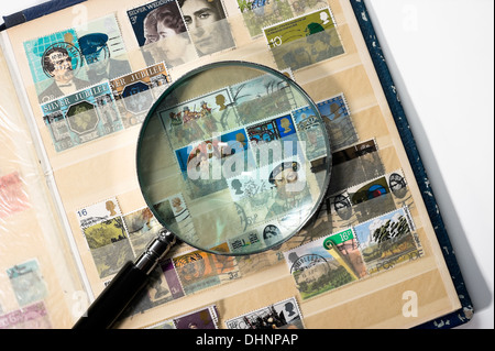 Postage stamp collection album with a magnifying glass on it - Stock Photo