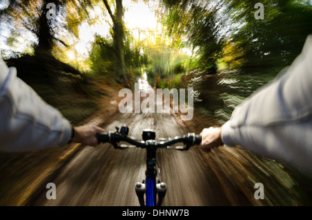 View over the handle bars along tree lined muddy bridal path country lane steep banks going fast towards sunshine - Stock Photo