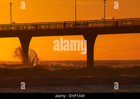 Waves hitting New Brighton Pier at Dawn, Christchurch, South Island, New Zealand - Stock Photo