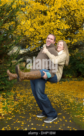 Vertical photo of happy adult couple with husband giving his wife a piggy back ride in the park during a nice day - Stock Photo