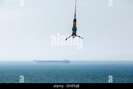 Netherlands, Scheveningen, near The Hague. Bungee jumping from Pier. Boat in background - Stock Photo