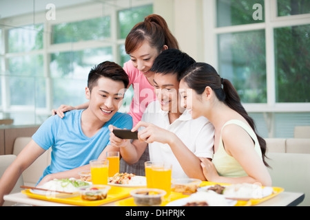 Young adults photographing foods in restaurant - Stock Photo