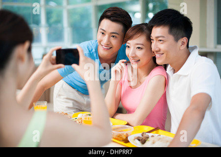 Young adults taking pictures in restaurant - Stock Photo