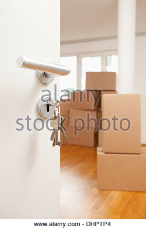 Empty room cardboard boxes door keys moving in out - Stock Photo