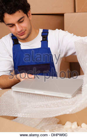 man young new home unpacking moving in boxes - Stock Photo