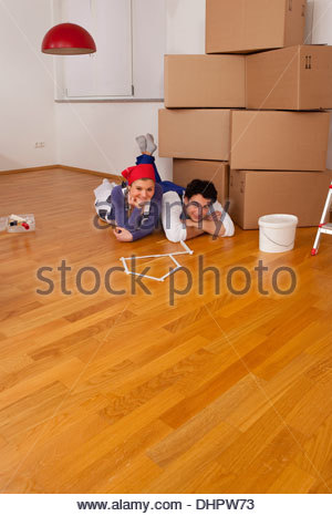 Young couple together loving moving home in boxes - Stock Photo