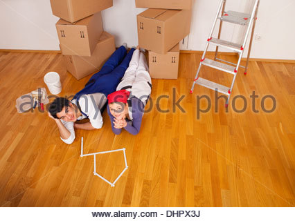 young couple new home house moving in boxes tired - Stock Photo