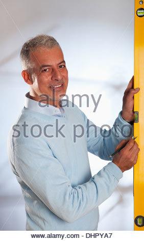 Architect man engineer holding using spirit level - Stock Photo