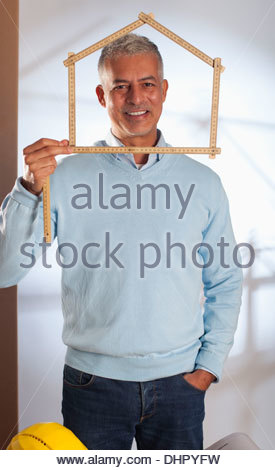 Architect holding ruler in shape of model house - Stock Photo