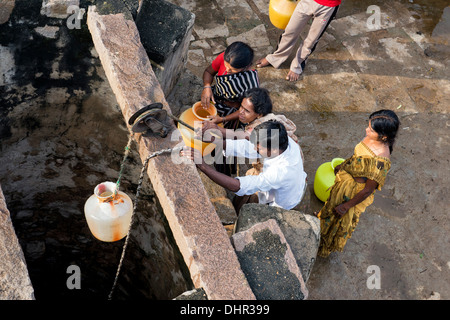 Indian women and men drawing water from a well in a rural Indian village street. Andhra Pradesh, India - Stock Photo