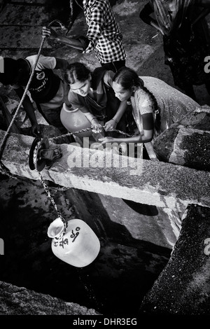 Indian teenage girls and boys drawing water from a well in a rural Indian village street. Andhra Pradesh, India - Stock Photo