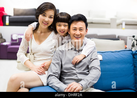 Cheerful family sitting in couch in furniture shop - Stock Photo