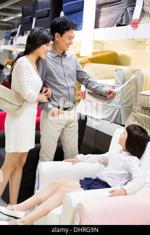 Happy family shopping in furniture shop - Stock Photo