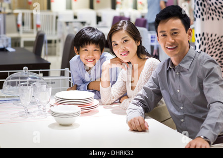 Cheerful family sitting side by side and smiling - Stock Photo