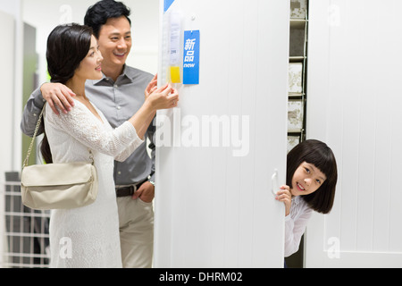 Girl hiding in wardrobe while parents checking the price tag - Stock Photo