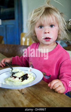 Little boy with his face smeared by Semolina pudding - Stock Photo