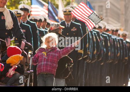 A child of a New York area Coast Guard service member waves the American Flag while marching in New York City's - Stock Photo