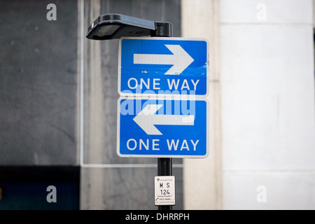 Two one-way traffic signs mounted one above the other but both pointing in opposite directions. London, UK. - Stock Photo