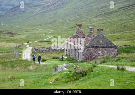 Walkers pass by a ruined croft on a stretch of the West Highland Way between Kinlochleven and Fort William. - Stock Photo