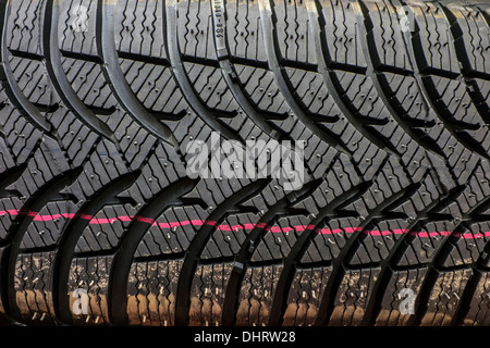 Close up of new winter tire / snow tyre for car showing rubber tread profile with deep grooves and additional sipes - Stock Photo